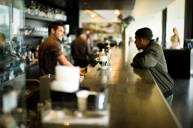Un barman et un client en train de discuter