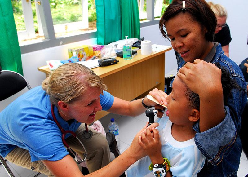 Une pédiatre examine un enfant, dans les bras de sa mère.